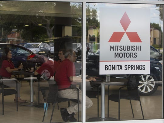 Staff members work inside the Mitsubishi showroom in