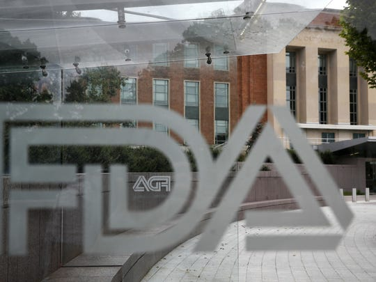 ​This Thursday, Aug. 2, 2018 photo shows the U.S. Food and Drug Administration building behind FDA logos at a bus stop on the agency's campus in Silver Spring, Md.  ​