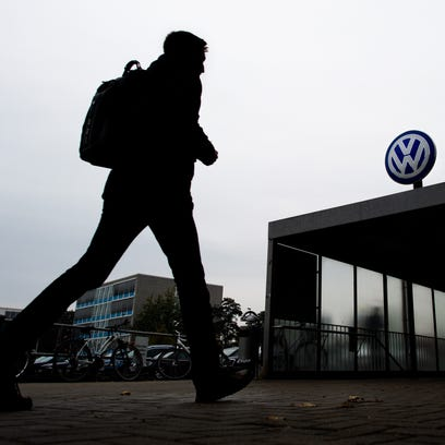 A VW employee enters the Volkswagen factory site through Gate 17 in Wolfsburg, Germany, Oct. 6, 2015.