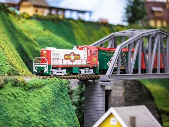 """This model train and holiday village display are part of the """"Nights of Lights"""" at McKee Botanical Garden."""
