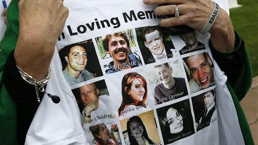 Sandy Phillips, whose daughter Jessica Ghawi was killed in the 2012 Aurora movie theatre massacre, carries a T-shirt memorializing the twelve people killed in the attack, outside the Arapahoe County District Court following the day of closing arguments in the trial of theater shootings defendant James Holmes, in Centennial, Colo., Tuesday July 14, 2015. (AP Photo/Brennan Linsley)