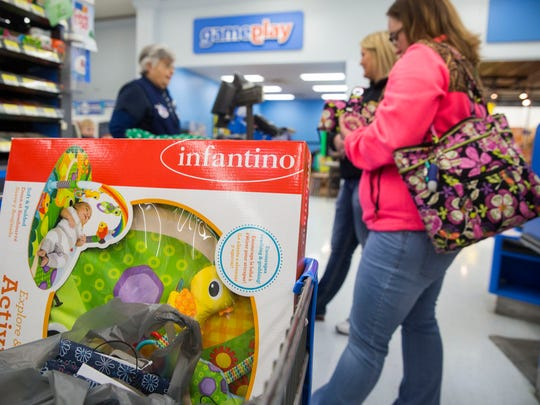 Leah Bond and Nicole Lyell purchase presents for families the Tulip Tree Family Health Care is helping out during the Christmas season on Sunday afternoon at Walmart.