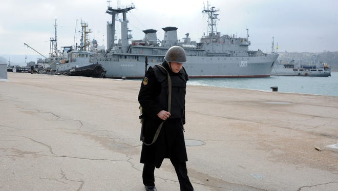 A Russian sailor walks in front of the Slavutych Ukrainian navy ship moored in Sevastopol bay on Thursday.