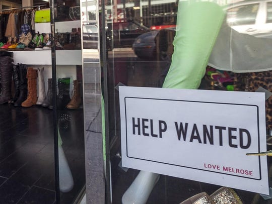 A help wanted sign is shown on display at a clothing