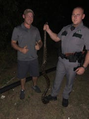 Kevin Dinger Jr., left, stands next to a Collier County Sheriff's deputy after they caught a python near Lely on Tuesday, Dec. 5, 2017.