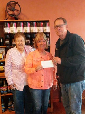 Chairperson for Youth Kiwanis Services Jerry Medema and Kiwanis member Joanne Kahl hand Educational Foundation secretary Lynn Hartgerink a check.