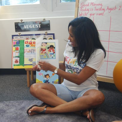 Cincinnati Country Day School kindergarten teacher Angela Joiner, right, shares a story with her class. Among her students are Christopher Hildebrant, left, of Mason.