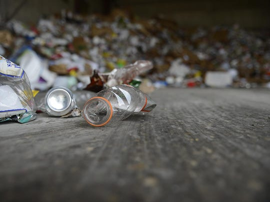 Recyclables lay on the ground at the Brown County Resource
