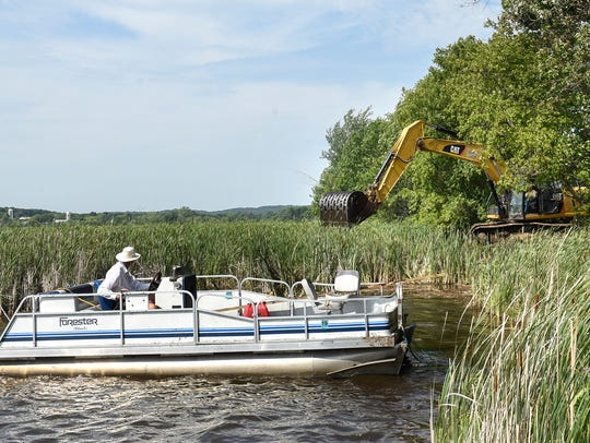 A pontoon boat moves bogs into place so that they can