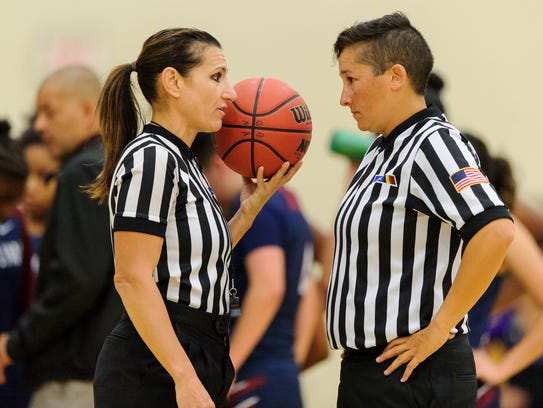 Referees discuss a technical foul in a girls high school