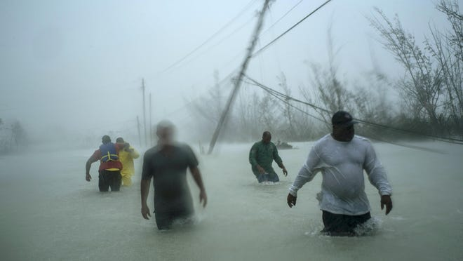 Volunteers walk under the wind and rain of Hurricane Dorian, on a flooded road after rescuing several families that arrived on small boats in Freeport, Grand Bahama, Bahamas, after the Category 5 storm destroyed thousands of homes, crippled hospitals and likely killed hundreds of people.