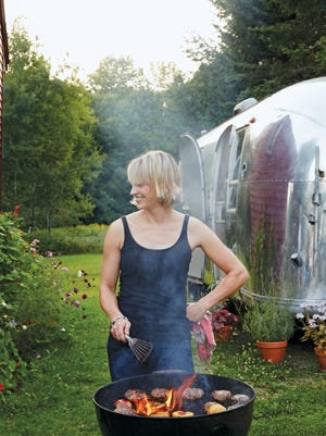 Erin French, owner of The Lost Kitchen restaurant in Freedom, Maine, grilling burgers with an Airstream trailer in the background.