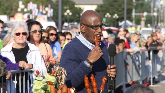 Al Roker takes a bite of the Bacon Wrapped Riblet On-A-Stick during the 2013 Iowa State Fair.