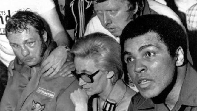 American heavyweight boxer Muhammad Ali, right, talks to newsmen after the fight with Belgian heavyweight Jean-Pierre Coopman, left, who he knocked out in the fifth round, in San Juan, Puerto Rico, Feb. 21, 1976. Coopman's wife sits between the two fighters.