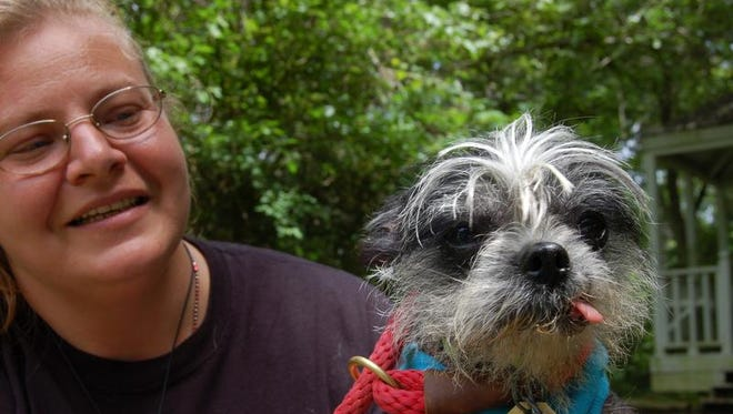 Carolyn Carter, shelter manager at the Humane Society of North Central Arkansas, takes Ferbie, a 15-year-old Chinese Crested, outside for a little sun.