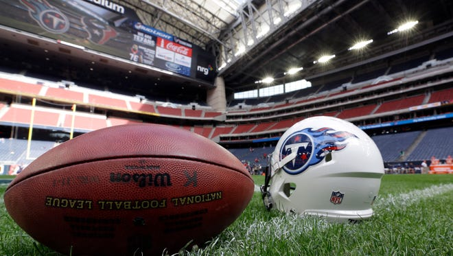 A football and Tennessee Titans helmet sit on the field before an NFL football game against the Houston Texans Sunday, Nov. 30, 2014, in Houston. (AP Photo/David J. Phillip)