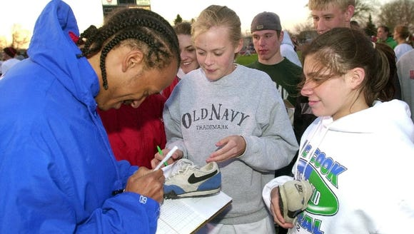 Isaiah Fluellen (left) autographs a pair of track shoes