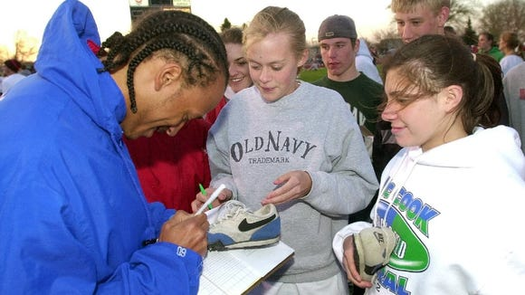 Isaiah Fluellen (left) autographs a pair of track shoes for another athlete at the 2002 Dakota Relays. The American standout from Germany pulled his hamstring in a 100-meter heat.