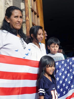 Jeanette Vizguerra of Denver poses with three of her U.S. citizen children — Zury, Luna and Roberto — in the doorway of the First Unitarian Society of Denver where she has taken sanctuary. Vizguerra, an undocumented immigrant, was worried that a regular meeting with U.S. immigration officials would result in her deportation.