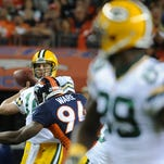 Green Bay Packers quarterback Aaron Rodgers (12) throws downfield for wide receiver James Jones (89) as he is hit by Denver Broncos outside linebacker DeMarcus Ware (94) in a November game.
