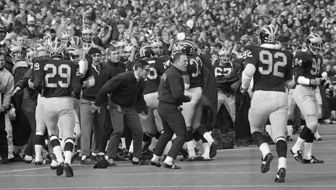 Players on the Michigan sideline are excited playing against the defending national champions in 1969.
