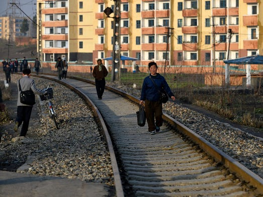 People walk on a rail tracks in Pyongyang, April 18,