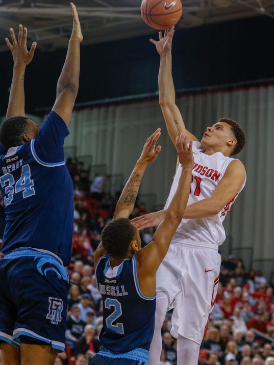Davidson guard Kellan Grady, right, shoots over Rhode Island guard Fatts Russell, center, and forward Andre Barry in the first half of an NCAA college basketball game in Davidson, N.C., Friday, March 2, 2018. (AP Photo/Nell Redmond)