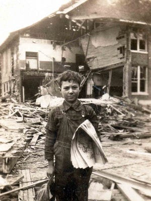 Clare Howery, 9, stands in front of the remains of the Bath Consolidated School, a week after the bombing.