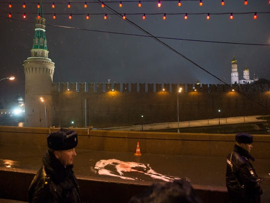 Russian police officers stand next to trace of the