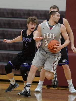Indiana University East's Parker Salinas moves the ball against Asbury's Will Henderson during the KIAC basketball tournament Wednesday, Feb. 24, 2016, at Earlham College in Richmond.