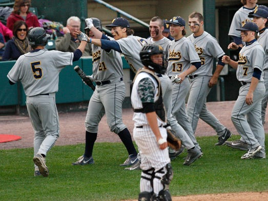 Victor's Dale Wickham, 5, far left, is greeted by teammates as he scores on a groundout by teammate Mike Wagner in the first inning as Greece Athena catcher Jack Vivinetto looks away during their Section V Class AA baseball final Thursday, May 29, 2014 at Frontier Field in Rochester.