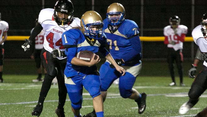 Jensine Falu-Montes with Webster Schroeder runs with the ball Sept. 24 against Wilson.