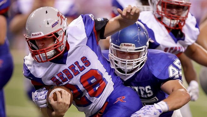 Roncallli's Kenny Gillum (28) runs by Franklin Central's Chris Ford for a touchdown. The Franklin Central Flashes played the Roncallli Rebels in high school football Friday, August 26, 2015, evening at Lucas Oil Stadium.