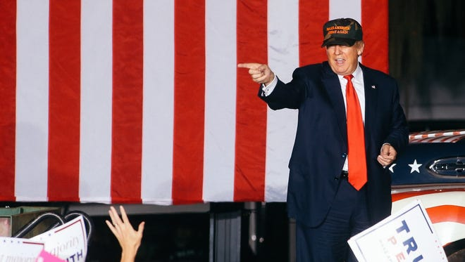 Donald Trump points at supporters after speaking at a rally at the Tallahassee Automobile Museum on Tuesday, October 25, 2016.