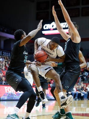Cincinnati's Kevin Johnson, center, drives between Tulane's Melvin Frazier, left, and Ryan Smith, right, during the first half of an NCAA college basketball game, Sunday, Jan. 1, 2017, in Cincinnati.