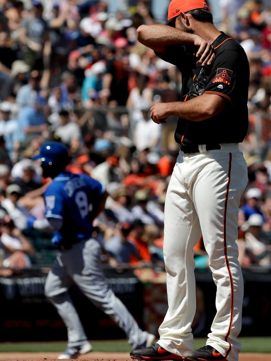 Kansas City Royals' Cheslor Cuthbert, left, rounds the bases after a home run off San Francisco Giants starting pitcher Madison Bumgarner, right, during the second inning of a spring baseball game in Scottsdale, Ariz., Friday, March 23, 2018. (AP Photo/Chris Carlson)