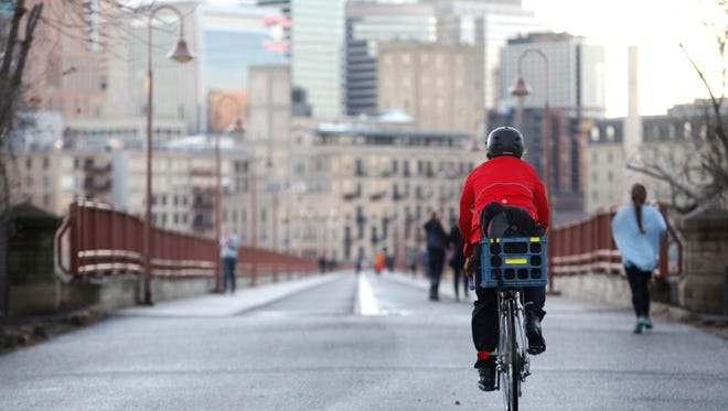 A cyclist approaches the Stone Arch Bridge on the north side of downtown Minneapolis. The former railroad bridge over the Mississippi River has dedicated walking and biking lanes and prohibits motorized vehicles.