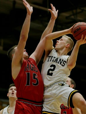 UW-Oshkosh Titan's Ben Boots goes in for a shot against Edgewood's Emil Radisevic.  UW-Oshkosh Titan men took on Edgewood College at Kolf Sports Center, November 22, 2017.
