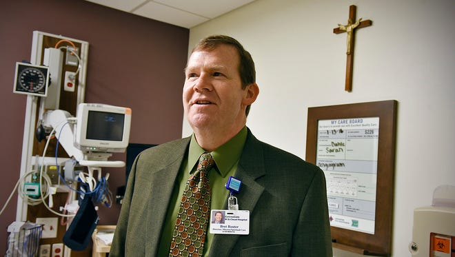 Bret Reuter, director of mission and spiritual care at St. Cloud Hospital, shows a crucifix Thursday, Jan. 14 which is placed in a patient room. The St. Cloud Hospital has a policy to take down a crucifix from a patients room if requested.