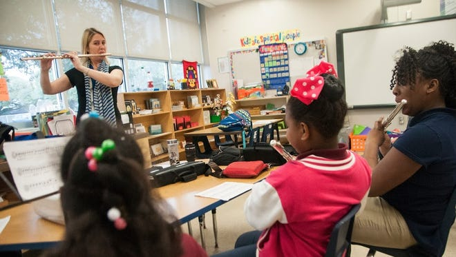 Kids' Orchestra flute teacher Suzanne Buerkle educates students (from left to right) Shirley Bell of Capitol Elementary, Jayna Davis of Captiol Elementary and Sha'Kyra Dupas of Belfair Montessori Magnet.
