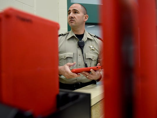 Lt. Mike Mattson with Minnehaha County Jail is framed between a charging stations for tablet computers on Tuesday at the jail. The tablets are a new option provided to inmates for a small fee.