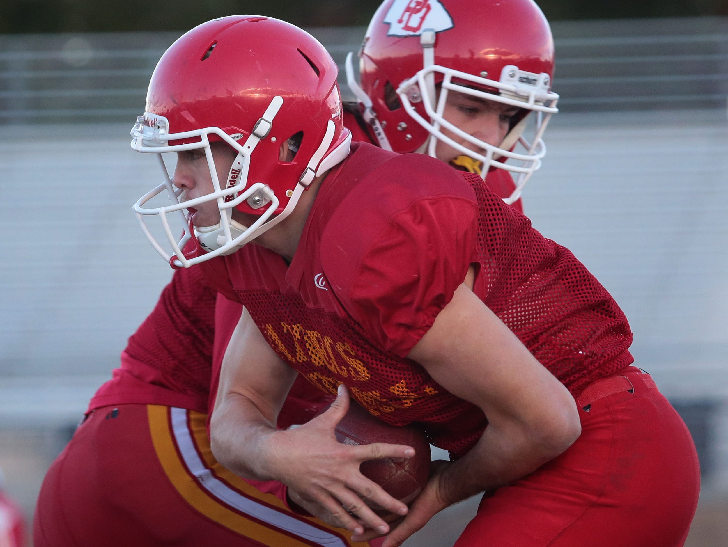 Palm Desert football player Beau Berryhill is handed the ball by quarterback Brian Devlin at practice on Wednesday at Palm Desert High School.