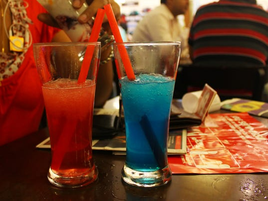 red and blue iced smoothie in long glasses with straws on table