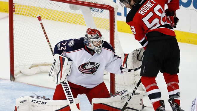 Columbus Blue Jackets goalie Sergei Bobrovsky, of Russia, left, tries to glove the puck as New Jersey Devils center Kevin Rooney (58) attacks during the third period of an NHL hockey game, Sunday, March 5, 2017, in Newark, N.J. The Blue Jackets won 3-0. (AP Photo/Julio Cortez)