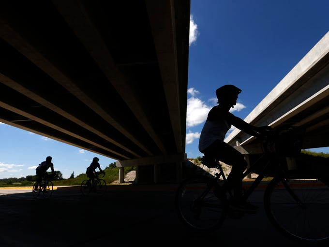 Cyclists make their way under the US 169 overpass Monday,