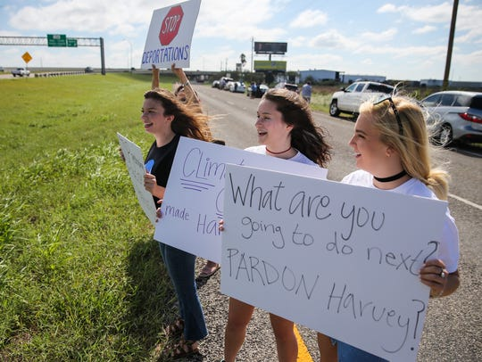 Protestors hold up signs along the highway while waiting