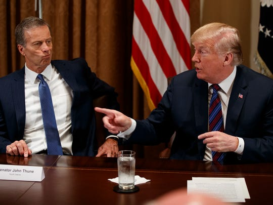 Sen. John Thune, R-S.D., listens as President Donald Trump speaks during a meeting with governors and lawmakers in the Cabinet Room of the White House.