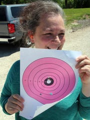 Ramona Collett of Butler proudly holds a paper target with evidence of bull's-eyes she shot with a handgun at Take Aim at Cancer, an event for cancer patients and their families at Schultz Resort Rod and Gun Club in Muskego. Collette's son Rober Collett of Sussex has been treated for Hodgkin's lymphoma.