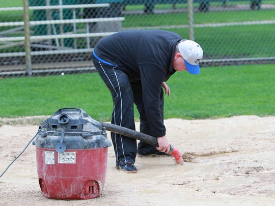Dodgers head coach Dave Rezek vacuums up water around home plate before their game with the Red Sox. This is the 60th anniversary season of the Raccoon Valley Little League.