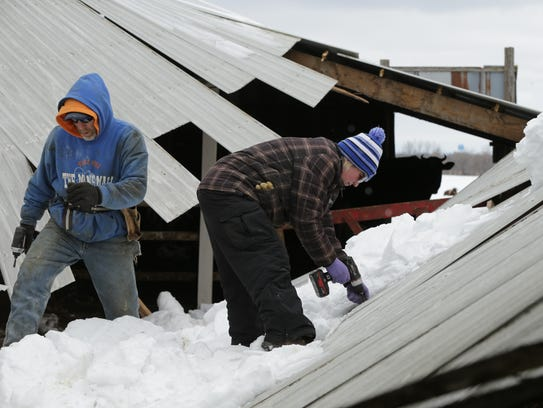 Jennifer and John Yost III, take apart their barn roof